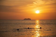 Cruise liner on the horizon against the setting sun. In the sea Royalty Free Stock Photography