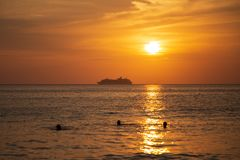Cruise liner on the horizon against the setting sun. In the sea Stock Photo