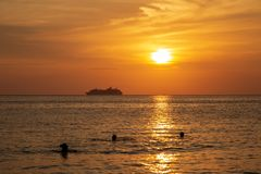 Cruise liner on the horizon against the setting sun. In the sea Royalty Free Stock Photos