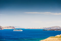 Cruise liner near the Greek Islands. Bright turquoise sea and blue sky. Santorini island, Greece Royalty Free Stock Photo