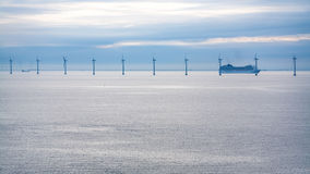Cruise liner near offshore wind farm in morning Royalty Free Stock Photography