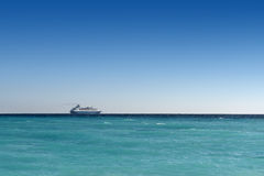 Cruise liner sailing away. On turquoise water and blue sky backround Royalty Free Stock Photos
