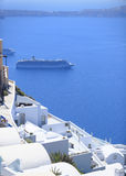 Cruise liner by Santorini island. Scenic view of cruise liner on coastline of Santorini island with traditional white buildings in foreground, Greece stock photo