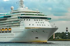Cruise liner at summer. White cruise liner moving to the sea at cloudy day Stock Image