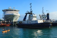 A cruise liner, tugboats, and kayakers in a harbor stock images