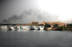 Cruise liners on Nile river, egypt. Cruise lioners on Nile river and brown smoke royalty free stock images