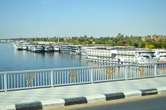Cruise liners on the Nile River. Luxor, Egypt - 17th May, 2018: View from the bridge to the Nile River. Cruise liners at the pier near the coast. Thick tropical stock images
