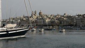 The cruise Luzzu boat swimms by and yacht marina. Birgu, Malta stock footage