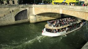 Cruise on river Seine. Paris, France - July 1, 2017: Bateaux-Mouches with many tourist during a trip on the Seine river, under Pont Saint Michel. Cathedral of stock video footage