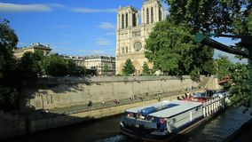 Cruise on Seine river. Paris, France - July 1, 2017: empty Bateaux-Mouches docked on the Seine under the red bridge with Notre Dame Cathedral on the Ile de la stock video