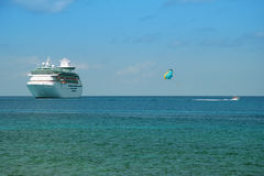 Cruise ship. Huge cruise ship in tropical waters with parasail Royalty Free Stock Photography