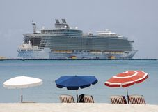 Cruise ship. Umbrellas on the beach with ship in the background Stock Image