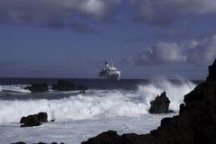 Cruise ship. Luxury cruise ship at sea with waves crashing against rocks Stock Photography