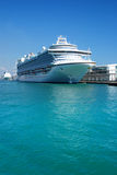 Cruise ship. A view across calm blue water at a large passenger cruise ship at a dock