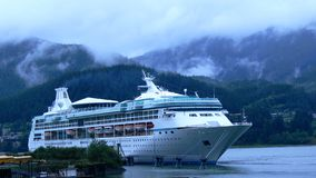 Cruise ship Alaska. Cruise ship docked in Alaska with misty mountains as background royalty free stock images
