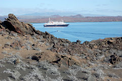 Cruise ship anchored in Sullivan Bay, Galapagos. Arid volcanic landscape with cruise ship anchored in Sullivan Bay, Galapagos Stock Images