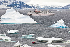 Cruise ship in Antarctia. Antarctic landscape with zodiac, icebergs and cruise ship in front of the mountains Royalty Free Stock Image