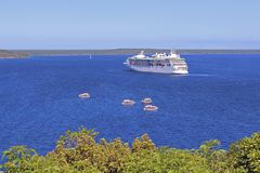 Cruise ship awaiting for tsunami, Lifou, South Pacific. Cruise ship and tender boats awaiting for tsunami, Lifou, South Pacific stock photo