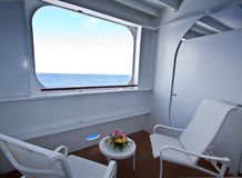 Cruise ship Balcony. A wide angle image looking out to sea on a cruise ship Balcony with deck chairs and contrasting flower arrangement on a table Royalty Free Stock Photos
