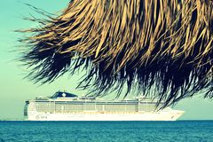 Cruise ship and beach umbrella Stock Images