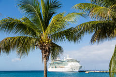 Cruise Ship on Blue Beyond Palm Trees. White Luxury cruise ship in blue water beyond palm trees Royalty Free Stock Photography