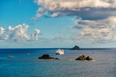 Cruise ship in blue sea on cloudy sky in gustavia, st.barts. Travel by water, discovery and adventure. Vessel and marine. Transport. Summer vacation and holiday royalty free stock image