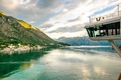 Cruise ship bridge in Montenegro Kotor Bay looking at scenic village with tall mountains during sunrise. Sun is shining on mountain stock photo