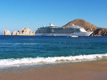 Cruise ship at Cabo San Lucas. Huge cruise ship anchoring outside the harbor in front of the beach. Blue sky and calm ocean, a perfect holiday Royalty Free Stock Photography