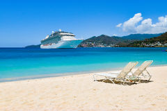 Cruise ship in Caribbean Sea with beach chairs on white sandy beach. Summer travel concept. Cruise ship anchored in the Caribbean Royalty Free Stock Image