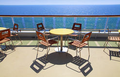 Cruise ship deck cafe. With table and chairs and beautiful ocean view Stock Photos