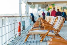 Cruise Ship Deck Chairs. Cruise Ship Wooden Deck Chairs and Some Senior Tourists stock photography