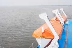 Cruise ship deck. Lifeboats covered by orange fabric. View of the grey water royalty free stock image