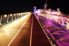 Cruise ship deck at night. Colorful sunbeds and running track on the deck of a cruise ship at night Royalty Free Stock Photo