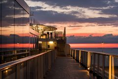 Cruise ship deck at sunset. Reflections of the sunset in the windows of a modern cruise ship at dusk Royalty Free Stock Photos