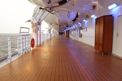 Cruise ship deck with wooden floor and turned. Cruise ship deck with wooden brown floor and turned on lamps at side stock photo