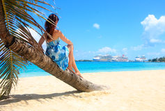 Cruise ship destination. A girl sitting on a bending palm tree facing a port with several big cruise ships Royalty Free Stock Photos