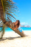 Cruise ship destination. A girl sitting on a bending palm tree facing a port with several big cruise ships Stock Images