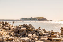 Cruise Ship in Distance Beyond Stacked Stones Royalty Free Stock Photos