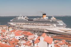 A cruise ship is docked at the port of Lisbon, Portugal. The cruise is over the Tejo River, near the mouth of the Atlantic Ocean. stock photo