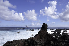 Cruise ship at Easter Island. Luxury cruise ship at sea with volcanic rocks in foreground. Taken at Easter Island Royalty Free Stock Image