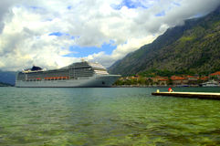 Cruise ship in emerald bay water. Luxury cruise ship anchored at Kotor harbor, against mountain and cloudy sky background.Kotor is a coastal town in Montenegro Stock Photos