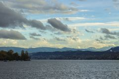 Lake Zurich landscape. Cloudy skyscape with snow covered Alps mountains peaks on horizon. stock photography