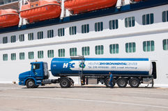 Cruise ship fueling. Gasoline Truck fuelling cruise ship Celebrity Reflection in Piraeus, Greece Royalty Free Stock Images