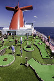 Cruise ship fun - Miniature golf at sea. Passengers enjoy playing miniature golf in the Caribbean Sea on the deck of the new Carnival Dream cruise ship Royalty Free Stock Photography