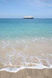 Cruise ship on the horizon of tropical beach. Cruise ship on the horizon of beautiful tropical beach in Bequia, Caribbean. Turquoise sea & sky, pale sand & stock photography