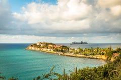 Cruise ship on the horizon with tropical resort of Sint Maarten. Philipsburg, Sint Maarten April 6, 2017: Tropical resort on the island built near the ruins of Stock Images