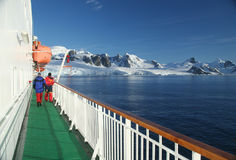 Cruise ship, icebreaker, with lifeboat. In calm seas, blue sky, with mountains & glaciers, Lemaire Channel, Antarctica Stock Photography