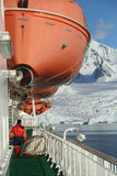 Cruise ship, icebreaker, with lifeboat. In calm seas, blue sky, with mountains & glaciers, Lemaire Channel, Antarctica Stock Image