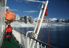 Cruise ship, icebreaker, with lifeboat. In calm seas, blue sky, with mountains & glaciers,  Lemaire Channel, Antarctica Stock Photo