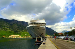 Cruise ship in Kotor,Montenegro. Luxury cruise ship anchored at Kotor harbor, against mountain and cloudy sky background.Kotor is a coastal town in Montenegro stock photography